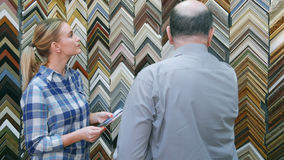 Ung kvinnlig klient som upp väljer en ram för en bild med en hjälp av den höga säljaren Royaltyfria Bilder