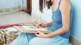 Ung kvinnlig konstnär som målar en ananas vid vattenfärger arkivfilmer