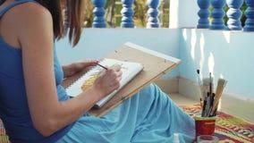 Ung kvinnlig konstnär som målar en ananas vid vattenfärger stock video