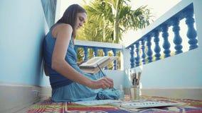Ung kvinnlig konstnär som målar en ananas vid vattenfärger lager videofilmer