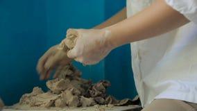 Ung kvinnlig konststudent som knådar och hugger lera lager videofilmer