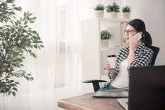 Ung kvinnlig kontorsarbetare som använder den mobila mobiltelefonen royaltyfri bild