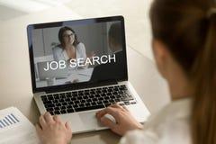 Ung kvinnlig kontorsarbetare som söker efter jobb på bärbara datorn royaltyfria foton