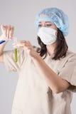 Ung kvinnlig labbpersonal som ser provröret med flytande Över Gr Royaltyfri Fotografi