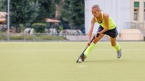 Ung kvinnlig ledande boll f?r landhockeyspelare i attack royaltyfria bilder