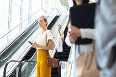 Ung kvinnlig ledare som tar rulltrappan medan rak Caucasian kvinnlig utövande blick framåt royaltyfri bild