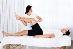 Ung kvinnlig massör som ger benmassage till mannen royaltyfri fotografi