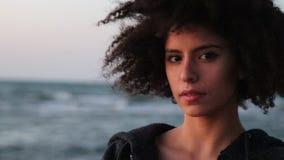 Ung kvinnlig med afro frisyrblick på kameran stock video