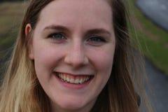 Ung kvinnlig med blåa ögon och det härliga leendet, utomhus- ståendeskott Åldrig markerade 20-25, caucasian och blondin Arkivbild