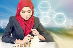 Ung kvinnlig med det säkra framsidauttryckt som sätter pengar in i spargrisen över abstrakt bakgrund Arkivbilder