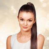 Ung kvinnlig med sunda glänsande bruna hår Arkivbild