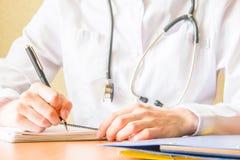 Ung kvinnlig medicinare som använder den moderna smartphonen i sjukhuset som skriver i anteckningsboken För slut handfors upp arkivfoton