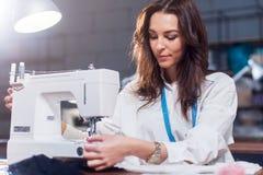 Ung kvinnlig modeformgivare som arbetar på symaskinen i ett seminarium arkivfoton