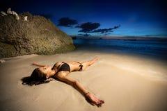 Ung kvinnlig modell som ligger i vatten på guld- solnedgång arkivbild