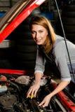 Ung kvinnlig motor för deltagare i utbildningfixandebil i garage arkivfoto
