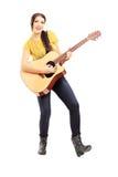 Ung kvinnlig musiker som spelar en akustisk gitarr Arkivbild