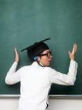 Ung kvinnlig nerd framme av svart tavla Royaltyfri Foto