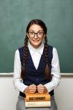 Ung kvinnlig nerd med böcker Arkivbilder