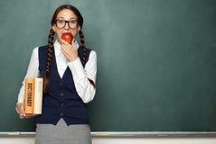 Ung kvinnlig nerd med böcker och äpplet Arkivfoton