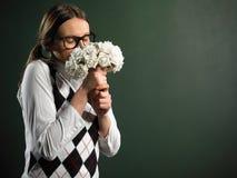 Ung kvinnlig nerd som luktar buketten av blommor Royaltyfri Fotografi