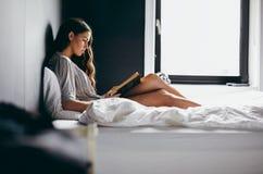 Ung kvinnlig på säng som läser en bok Royaltyfri Fotografi