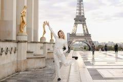 Ung kvinnlig person som går på Trocadero den fyrkantiga near förgyllda statyer och Eiffeltorn Royaltyfria Foton