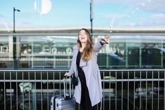 Ung kvinnlig person som stoppar taxien med den lyftt handen, valise och smartpone nära flygplats arkivfoto