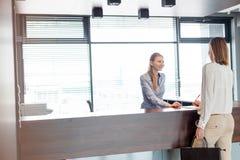 Ung kvinnlig receptionist som i regeringsställning ser det undertecknande dokumentet för affärskvinna arkivfoto
