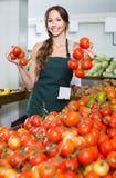 Ung kvinnlig säljare som rymmer nya mogna tomater Fotografering för Bildbyråer