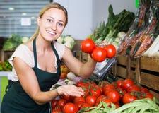 Ung kvinnlig säljare som rymmer nya mogna tomater på marknad Royaltyfri Bild