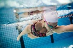 Ung kvinnlig simmaresimning i pöl arkivfoto