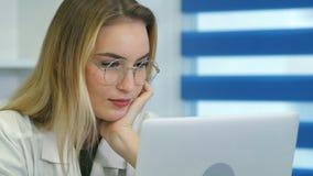 Ung kvinnlig sjuksköterska i exponeringsglas genom att använda bärbara datorn på skrivbordet i medicinskt kontor Royaltyfri Bild