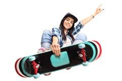 Ung kvinnlig skateboradåkare som utför ett trick Fotografering för Bildbyråer