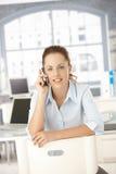 Ung kvinnlig som använder mobilen som i regeringsställning sitter Fotografering för Bildbyråer