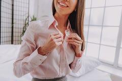 Ung kvinnlig som får klädd kläder för jobb royaltyfri foto