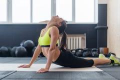 Ung kvinnlig som gör sträckning tillbaka av övningen, färdig kvinna som värmer upp i idrottshall Arkivfoto