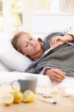 Ung kvinnlig som har influensa läggande i underlag Arkivbild