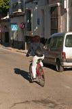 Ung kvinnlig som langer cykeln för att arbeta på den vakanta gatan i Spanien Arkivfoto