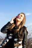 Ung kvinnlig som skrattar och talar på mobil Royaltyfri Bild