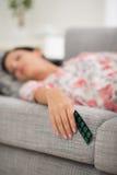 Ung kvinnlig som sovar med packen av pills Arkivbilder