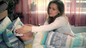 Ung kvinnlig som tar omsorg av hennes sjuka makeman i säng lager videofilmer
