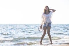 Ung kvinnlig som tycker om solig dag på den tropiska stranden Arkivfoton