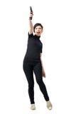 Ung kvinnlig spion i svartkläder med vapnet som skjuter upp i luft Royaltyfria Foton