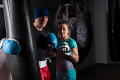 Ung kvinnlig spoty boxare i boxninghandskar som står med hennes trai Arkivbilder