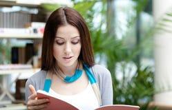 Ung kvinnlig student med böcker arkivbild