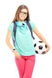 Ung kvinnlig student med ryggsäcken som rymmer en fotbollboll royaltyfria bilder