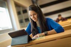 Ung kvinnlig student på universitetklassrumet Arkivbild