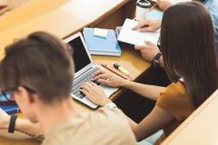 Ung kvinnlig student som använder den bärbara datoren på föreläsning arkivfoton