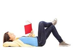 Ung kvinnlig student som ligger på ett golv och en läsning en roman Arkivbilder