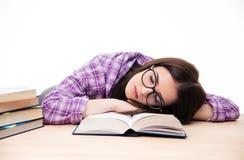 Ung kvinnlig student som sover på tabellen Royaltyfria Bilder